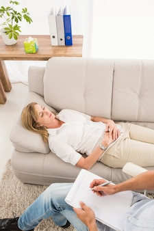 Unhappy woman lying on couch and talking to therapist