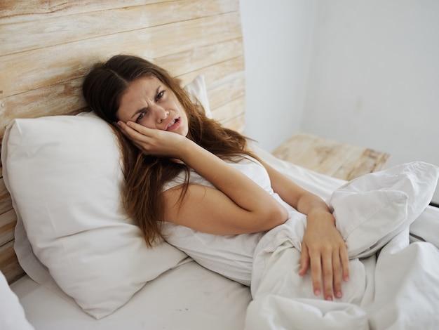 건강 문제를 느끼는 침대에 누워 있는 불행한 여자