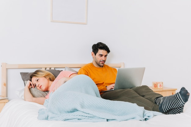 Unhappy woman lying near man with laptop