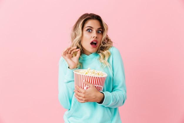 Несчастная женщина кричит и держит ведро с попкорном, изолированное над розовой стеной