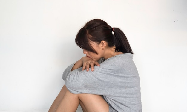 Unhappy woman sits and hugs her knees up to the chest, with upset and sad feeling