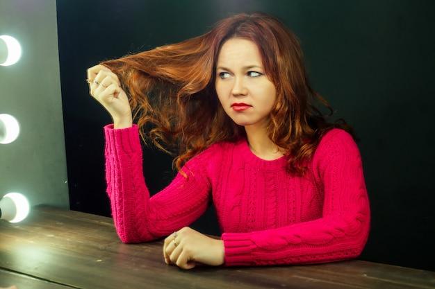불행한 여자는 미용실에 거울 앞에 앉아 나쁜 머리를 본다. 나쁜 미용실에서 그림과 머리 자르는 개념