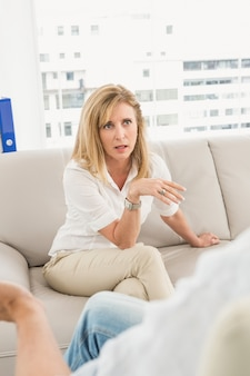 Unhappy woman sitting on couch and talking to therapist