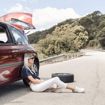 Unhappy woman sitting near the broken down car on winding road
