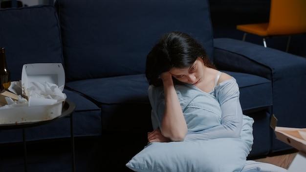 不安に苦しんでいる問題を考えて床に座っている不幸な女性
