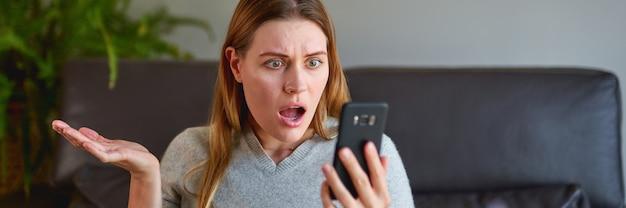 ノートパソコンでソファに座って、自宅で電話で話している不幸な女性。