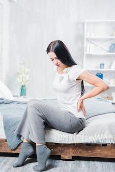Несчастная женщина, сидя на деревянной кровати страдает от боли в спине