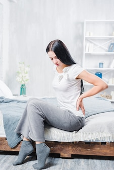 Unhappy woman sitting on wooden bed suffering from pain in back