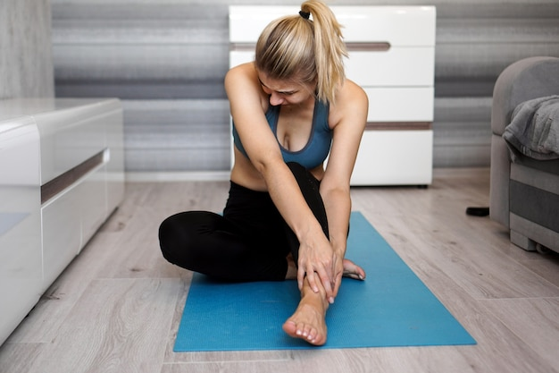Unhappy woman sitting on the yoga mat with ankle injury, feeling pain