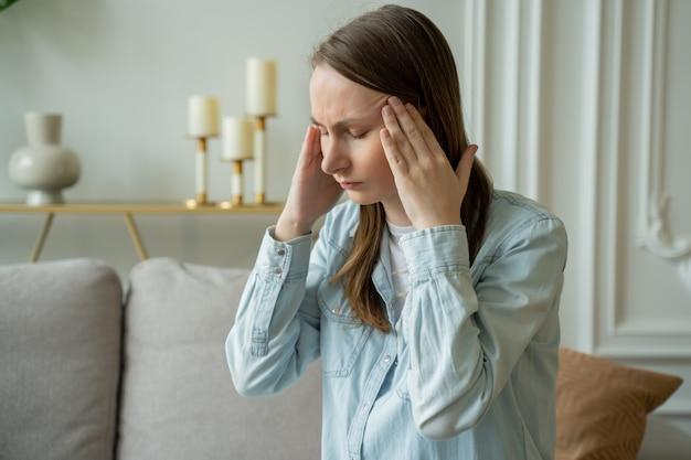 Несчастная женщина страдает от головной боли дома, сидя на диване Premium Фотографии