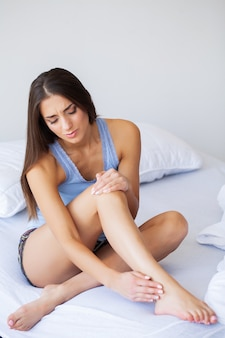 Unhappy woman suffering from pain in leg at home