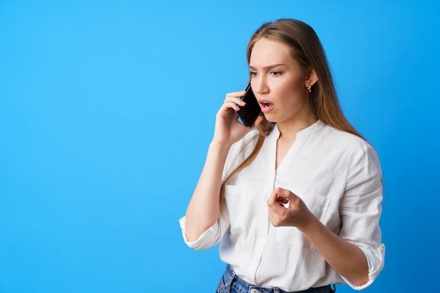 Несчастная женщина разговаривает по телефону с плохими новостями на синем фоне