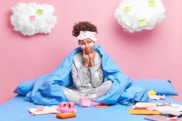 La donna infelice stanca del lavoro a distanza tiene le dita vicino all'angolo delle labbra in pigiama sul letto