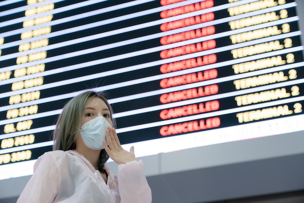 Unhappy woman traveler wearing mask looking flights cancellation status on flights information board in airport