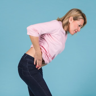 Unhappy woman with abdominal pain standing against blue backdrop