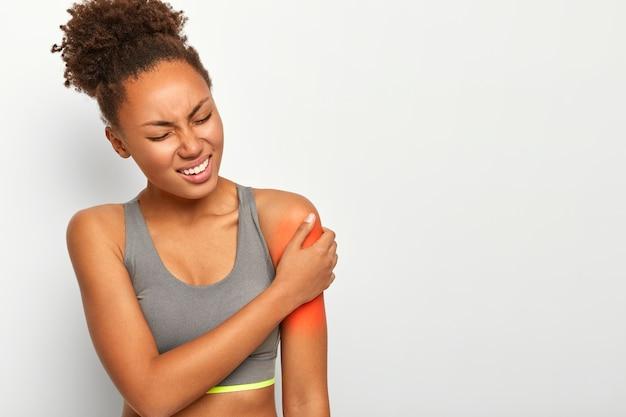곱슬 머리를 빗은 불행한 여자, 왼쪽 어깨에 고통스러운 감정이 있고, 이빨을 움켜 쥐고, 캐주얼 회색 스포츠 브래지어를 착용합니다.