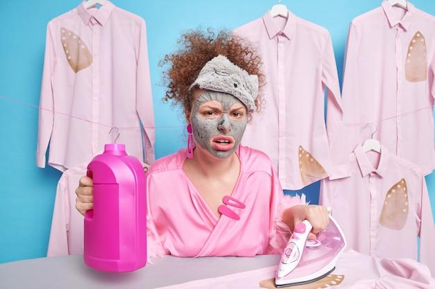 가정용 옷을 입은 곱슬 머리를 가진 불행한 여성이 세제 병을 들고 옷을 쓰다듬 기 위해 전기 다리미를 사용하여 미용 절차를 거칩니다. 집안일에 지친 불만족 주부
