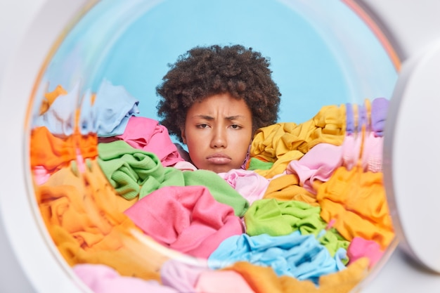Unhappy woman with curly hair has tired expression does laundry at home drowned in multicolored clothes shows only head feels discontent