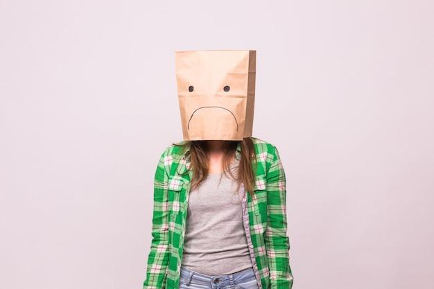 흰색 배경에 그녀의 머리에 종이 가방 앞에 슬픈 이모티콘으로 불행한 여자