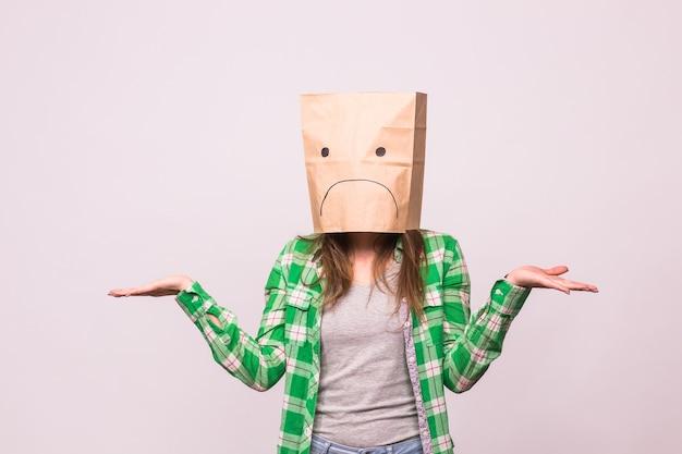 Несчастная женщина с грустным смайликом перед бумажным пакетом на голове на белом фоне