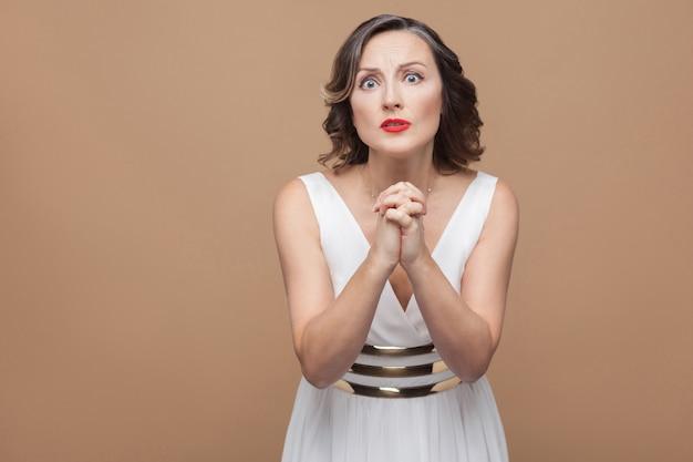 불행한 걱정된 여성은 미안하거나 카메라를 쳐다보세요. 흰 드레스, 붉은 입술, 짙은 곱슬머리를 한 감정적인 여성. 스튜디오 촬영, 실내, 베이지색 또는 밝은 갈색 배경에 격리