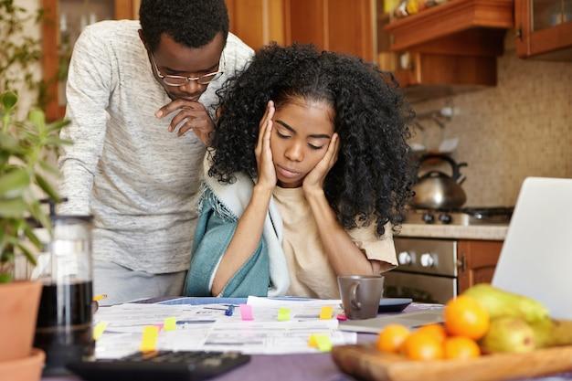 不幸な若いアフリカ人は家で請求書を計算している間ストレスと落ち込んでいるように見える