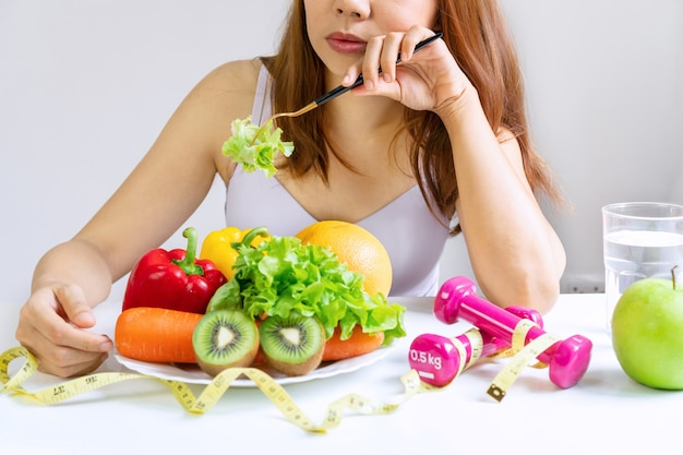 Unhappy young asian woman bored emotion on dieting time and refuse eating fresh green vegetables in fork on dining room at home, girl dislike taste of vegetable. healthy food concept. close up