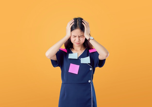 Unhappy young asian woman standing with holding hair and feeling confused with something