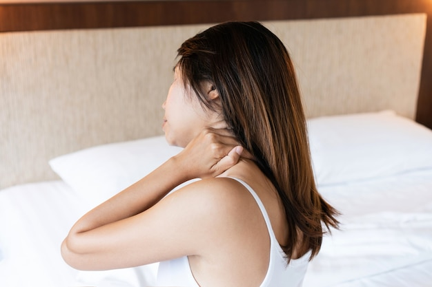 Unhappy young asian woman suffering from neck pain on bed after wake up in the morning