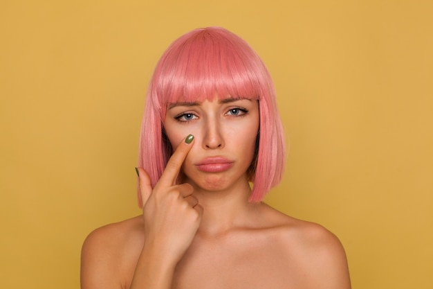 Unhappy young attractive pink haired female with bob hairstyle pouting her lips and looking sadly , holding forefinger under her eye while standing over mustard wall