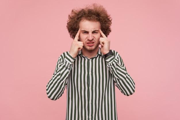 불행한 젊은 수염 난 곱슬 빨간 머리 남자는 그의 사원에 집게 손가락을 유지하고 강한 두통을 앓고있는 동안 얼굴을 찌푸리고 분홍색 벽 위에 서 있습니다.