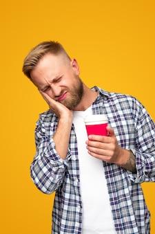 테이크 아웃 음료 한잔과 함께 캐주얼 옷에 불행한 젊은 수염 난 남자 손에 뺨에 손을 유지하고 노란색에 대한 치통으로 고통