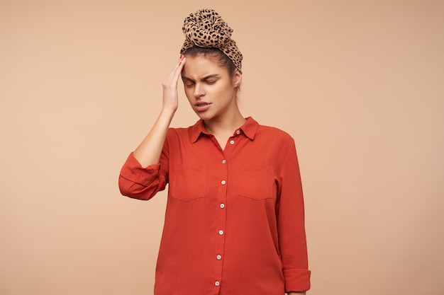 Unhappy young brunette woman wearing headband in knot while standing over beige wall in red shirt, keeping her eyes closed and raising hand to her head