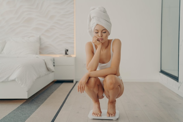 불행한 젊은 백인 여성은 침실에서 전자 저울 위에 발끝으로 쪼그리고 앉고 사랑스러운 얼굴에 슬픈 표정을 지으며 체중 증가를 보고 기뻐하지 않습니다. 다이어트와 체중 감량 개념