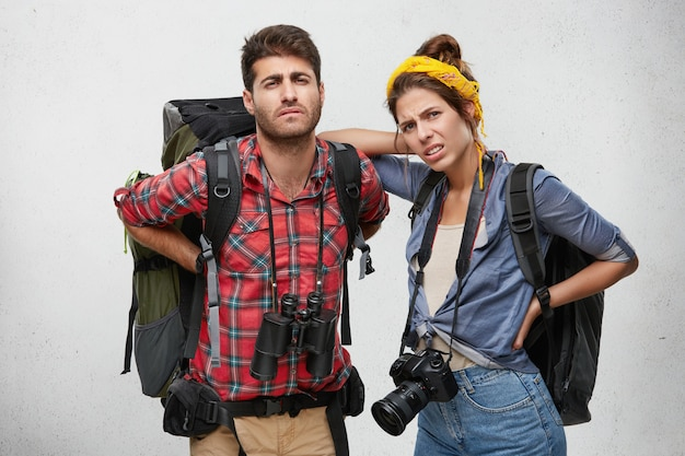 Unhappy young caucasian man and woman friends feeling exhuasted, having rest and massaging their aching backs after long climbing during backpacking trip, looking with painful expressions
