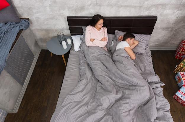 不幸な若いカップルは、ベッドに横になってパジャマを着て、寝室のキャンドルが灰色のロフトスタイルのベッドサイドテーブルの近くで議論の後に話していません