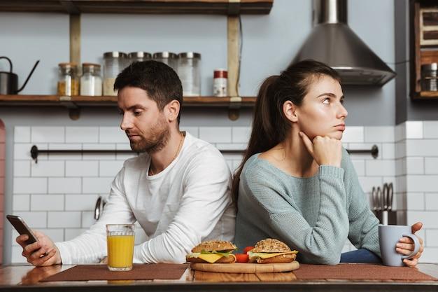 不幸な若いカップルが自宅で昼食時に台所に座って、問題を抱えている、携帯電話を持っている