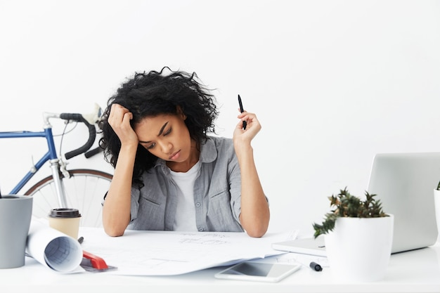 Unhappy young female engineer working from home on huge project