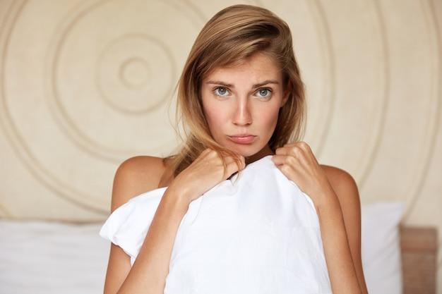 Unhappy young female feels abused after quarrel with husband, pouts lips and hides body with white pillow, has displeased expression and pleasant attractive appearance. woman poses in bedroom
