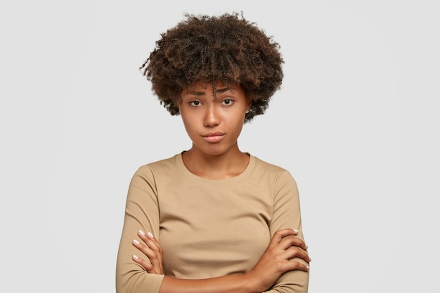 Unhappy young female model with afro bushy haircut has displeased facial expression, keeps hands crossed, listens negative news from interlocutor, wears casual beige sweater, stands indoor alone