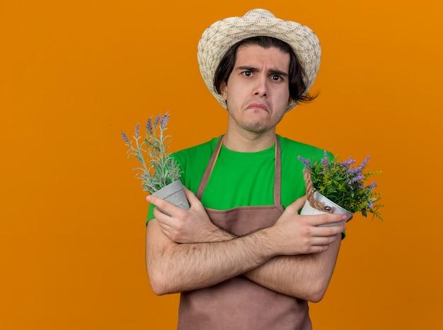 Infelice giovane giardiniere uomo in grembiule e cappello in possesso di piante in vaso che guarda l'obbiettivo con espressione triste in piedi su sfondo arancione