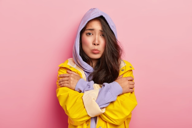 Unhappy young girl feels lonely and cold, looks sadly at camera, keeps hands crossed, wears hoody and raincoat, being dejected by bad weather