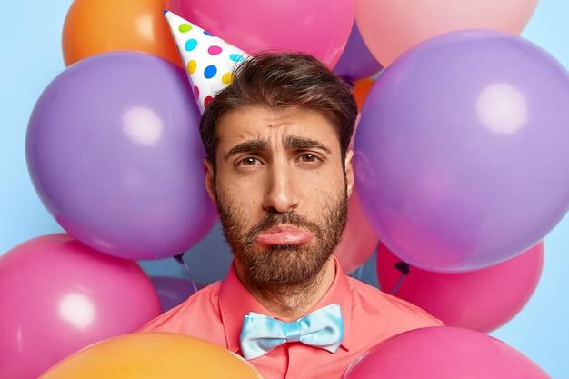 생일 다채로운 풍선에 둘러싸여 포즈 불행 한 젊은 남자