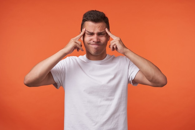 Unhappy young handsome brown haired man with short haircut keeping fingers on temples and frowning face while standing over orange background in white basic t-shirt