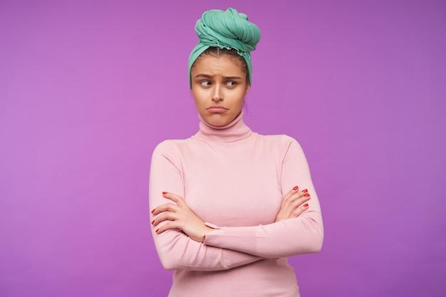 Несчастная молодая милая шатенка с мятной повязкой на голове, печально складывая губы, глядя в сторону и скрещивая руки на груди, изолирована над фиолетовой стеной