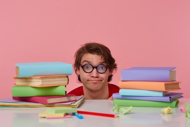Il giovane infelice con gli occhiali indossa una maglietta rossa, nascondendosi al tavolo con i libri, isolato su sfondo rosa. sembra dispiaciuto e triste.