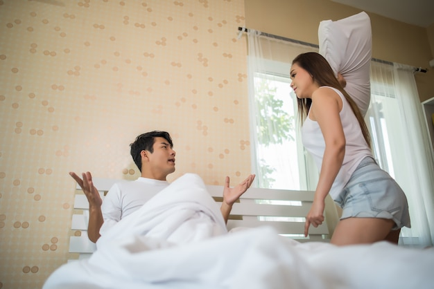 Unhappy young man having argument with his girlfriend in bed room