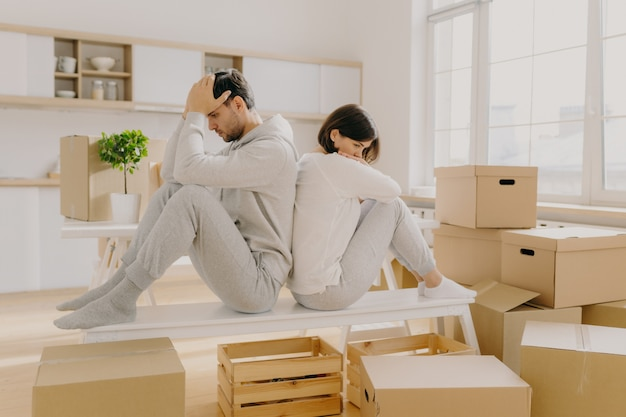 Unhappy young married woman and man have to leave house, move in other place, sit back to each other pose in empty room with stack of boxes, wear domestic clothes and socks, have some problems