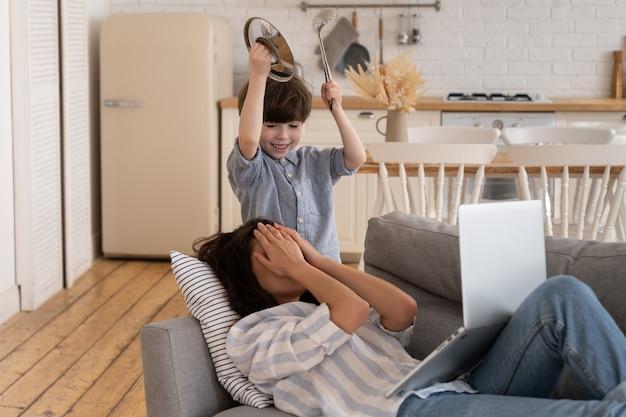 騒々しい小さな息子から手で不幸な若いお母さんが顔を覆う悪い行動ママは頭痛に苦しんで