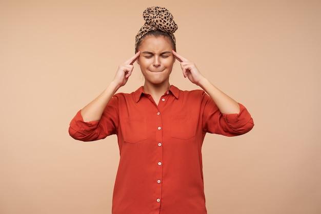 Giovane donna graziosa del brunette infelice con trucco naturale che tiene i suoi occhi chiusi e che si morde le labbra mentre soffre di mal di testa, isolato sopra il muro beige